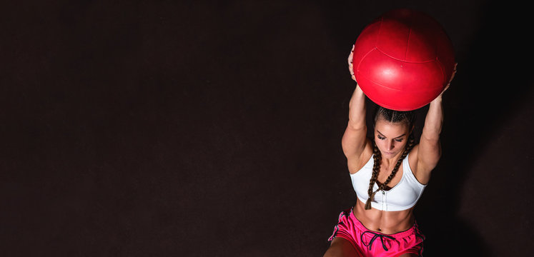 Young strong sweaty fit muscular girl with big muscles doing sit ups with medicine ball for abdominal muscles or abs hard crossfit workout training on the gym floor, Angled photo view from above