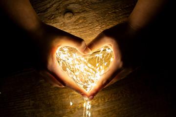 Leuchtendes Herz aus Lichterketten halten