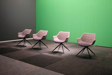 Four empty chairs in a TV studio with green screen background