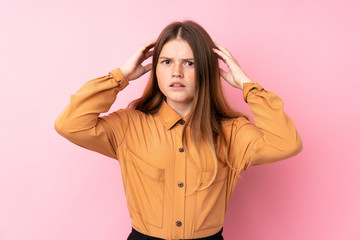 Ukrainian teenager girl over isolated pink background frustrated and takes hands on head