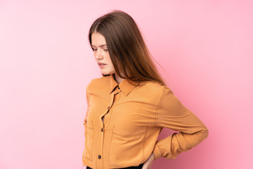 Ukrainian teenager girl over isolated pink background suffering from backache for having made an...