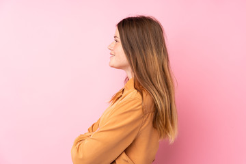 Ukrainian teenager girl over isolated pink background in lateral position