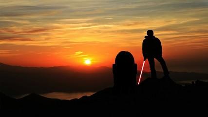 Fototapeta Silhouette Hiker Holding Laser Sword On Mountain Against Sky During Sunset