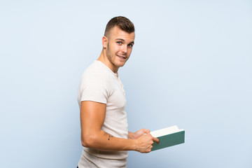 Young handsome blonde man over isolated blue background holding and reading a book