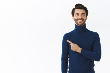Confident, good-looking happy smiling caucasian man with bristle in stylish high neck sweater,...