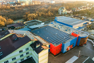 Aerial view of many photo voltaic solar panels mounted of industrial building roof. Wall mural
