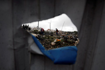 Palestinian demonstrators, seen through a hole in a metal panel, run during a protest against the U.S. President Donald Trump's Middle East peace plan, near the Jewish settlement of Beit El in the Israeli-occupied West Bank