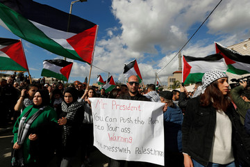 A man holds a banner as Israeli Arabs take part in a protest against the U.S. President Donald Trump's Middle East peace plan in the town of Baqa Al-Gharbiyye
