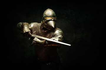 Portrait of a knight in armor, his sword in his hands, performing an attack parade