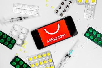Smartphone with Aliepress logo with pills and vaccine. Novel coronavirus 2019-nCoV.