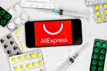 January 2020, China, Wuhan. Smartphone with Aliepress logo with pills and vaccine. China Trade Ban Concept. Novel coronavirus 2019-nCoV.