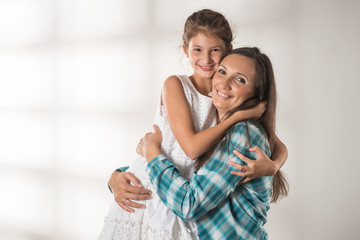 Young cheerful caring mother hugs her pretty positive daughter standing on a white background. concept in a warm relationship between children and parents. Place for advertising