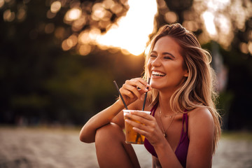 Close-up portrait of a beautiful happy young woman drinking on a beach. Summer vacation concept.