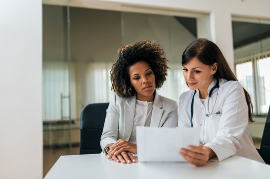 Medical exam. Portrait of a beautiful female doctor and patient looking at test results.
