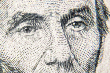 Abraham Abe Lincoln face on 5 dollar bill close up. Detail of new currency note. Macro view of...