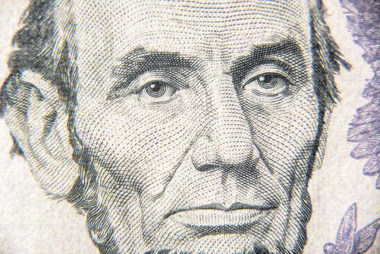 Abraham Abe Lincoln face on 5 dollar bill close up. Portrait of famous US president on dollar banknote. Macro view of USA paper money.