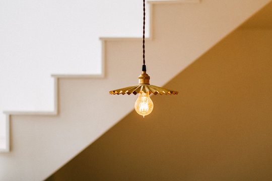 Low Angle View Of Illuminated Light Bulb Hanging Against Steps