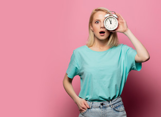 Beautiful blonde woman with alarm clock on pink background
