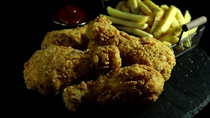 Fototapete - Breaded crispy fried chicken legs, french fries and sauce  on stone black surface rotation 360 degrees.