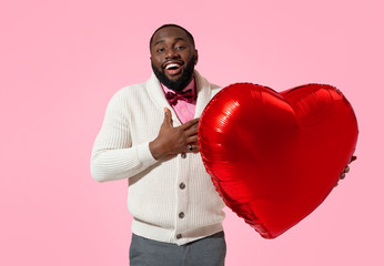 Happy man holds red heart shape balloon. Photo of handsome man in love on pink background. Valentine's Day