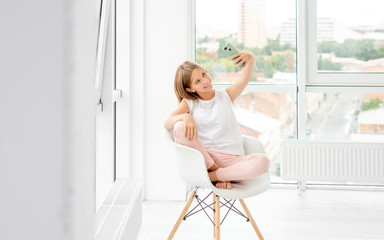 Young girl making selfie in soft chair indoors