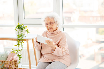 Aged woman in glasses with tablet