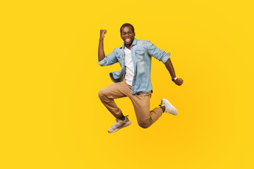 Full length portrait of joyous ecstatic man in denim shirt jumping for joy or flying with raised hand, gesturing yes i did it, celebrating success. indoor studio shot isolated on yellow background Fotobehang