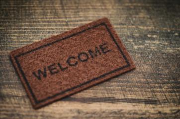 Old Welcome door mat on wooden background