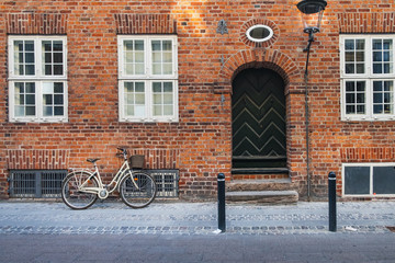 Photo sur Toile Velo Parked Bicycle in front of house in Copenhagen, Denmark. Red old brick house with wooden windows and metal arched carved door is located in historic part of Copenhagen