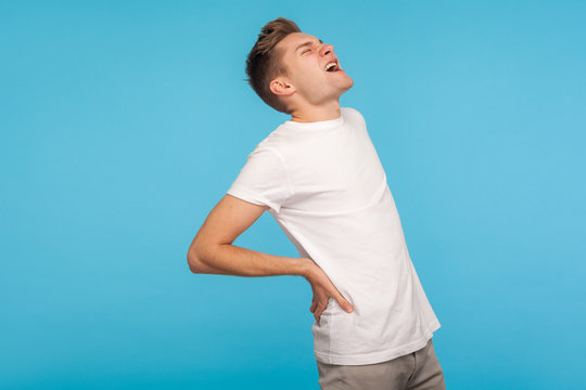 Acute back ache. Unhealthy man shouting from sudden pain in lower back, touching hurting spine, suffering from lumbar muscle strain, healthcare and medical concept. indoor studio shot, blue background