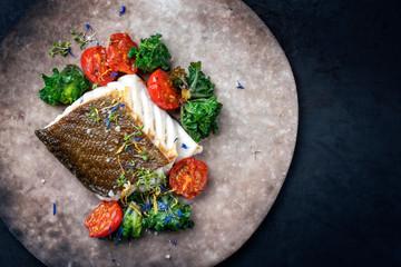 Gebratener europäisches Skrei Kabeljau Kisch Filet mit Kalette und Tomaten als Draufsicht auf einem Modern Design Teller mit Textfreiraum rechts Fotomurales