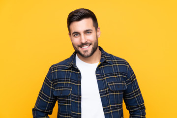 Young handsome man with beard over isolated yellow background laughing