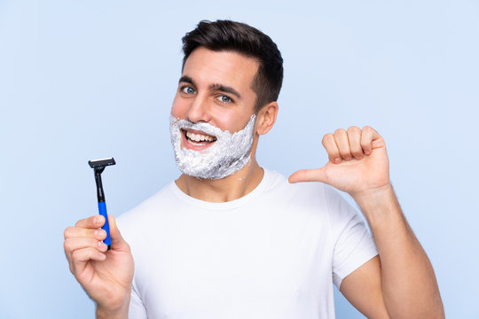 Young handsome man shaving his beard over isolated background proud and self-satisfied