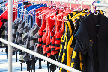Personal flotation device as a life jacket in store. Many bright life jackets hang in a row on hangers.
