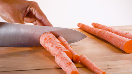 hand cutting carrots on cutting board white background