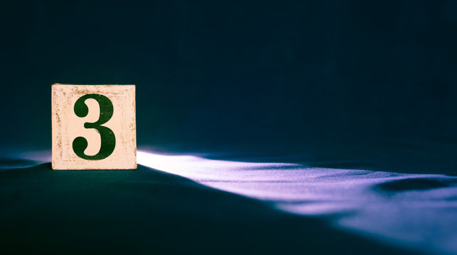 Rustic wooden block with number 3 - three - dark background