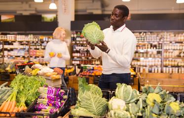 Adult African American man choosing vegetables