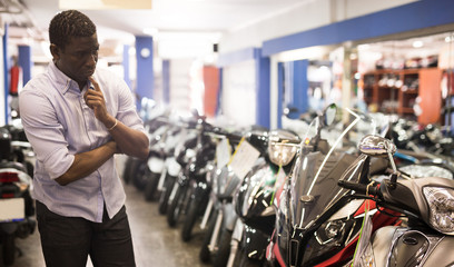 Portrait of adult man buying new motorcycle at modern showroom