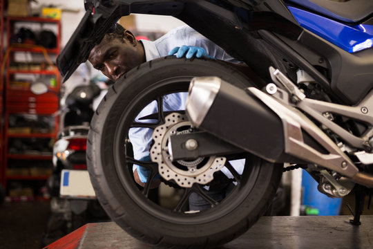 Afro american expert inspects the wheel of a motorcycle