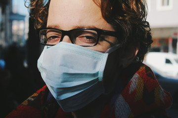 Close up of young man wearing surgical mask outdoors