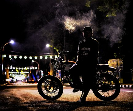 Full Length Of Man Sitting On Motorcycle At Night