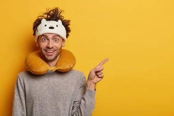 Positive male passenger wears sleepmask and travel pillow around neck, points away on blank space, shows advertisement with glad expression, stands against yellow wall. Traveling in transport