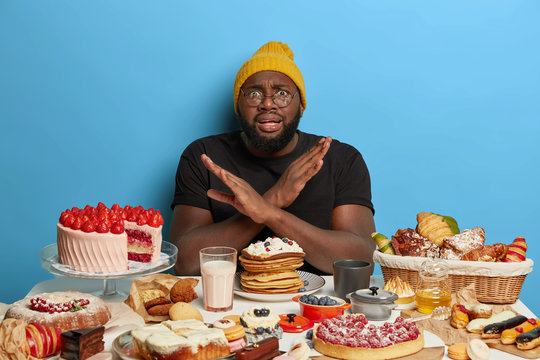 African American man crosses arms over chest, makes denial gesture, refuses eat sugary products, sits at table with bakery, keeps to diet, tries eat only healthy food, wears hat and t shirt.