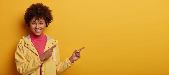 Check this out. Photo of attractive smiling woman with Afro hair points on copy space, has satisfied face expression, wears yellow anorak, isolated over yellow background, smiles with teeth.