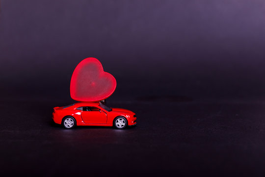 Valentine's day on dark background with miniature red toy car carrying a heart on black surface. Empty place for your text.
