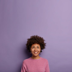 Good looking curious dark skinned woman looks with interest and smile above, imagines something hilarious, wears pink jumper, models over purple background, copy space upwards, believes in good future
