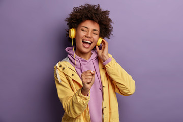 Lets enjoy sound of music. Upbeat cheerful woman holds hand as microphone, sings song and heart out, listens uses modern headphones, has overjoyed expression, being real meloman, dressed casually