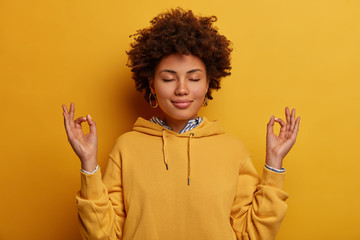 Poster de jardin Zen Portrait of ethnic woman stays calm, meditates and practices yoga, keeps hands in zen gesture, closes eyes, relaxes after hard working day, wears yellow sweatshirt, poses indoor, unites with nature