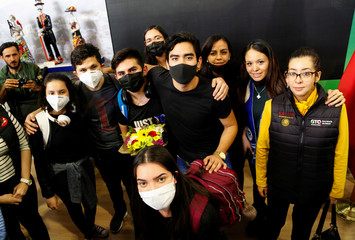Mexican students wearing protective masks pose for a picture upon their arrival at the Del Bajio International Airport, after the Guanajuato state government arranged their return from China due to the coronavirus outbreak, in Silao