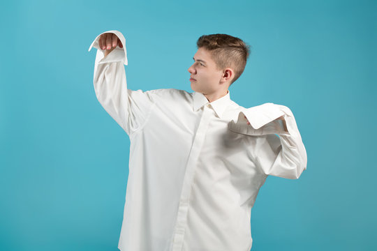 a young man in an oversized white shirt shows that his shirt is too big for him